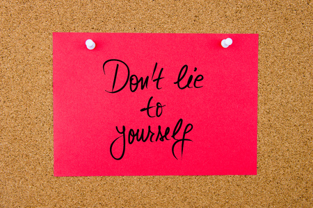 Red paper note with handwritten text Do Not Lie To Yourself pinned on cork board with white thumbtacks