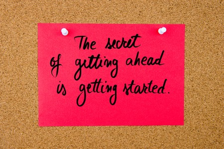 getting started: Red paper note with handwritten text The Secret Of Getting Ahead Is Getting Started pinned on cork board with white thumbtacks