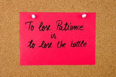 paciencia: Nota de papel rojo con el texto escrito a mano a perder la paciencia es perder la batalla depositado en el tabl�n de corcho con chinchetas blancas