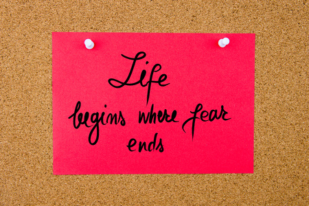 begins: Red paper note with handwritten text Life Begins Where Fear Ends pinned on cork board with white thumbtacks