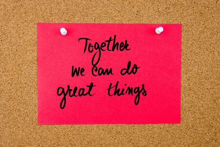 Red paper note with handwritten text Together We Can Do Great Things pinned on cork board with white thumbtacks