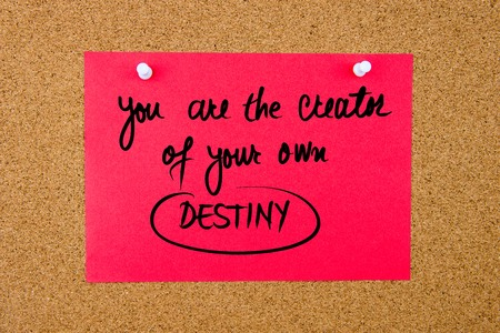 creator: Red paper note with handwritten text You Are The Creator Of Your Own Destiny pinned on cork board with white thumbtacks