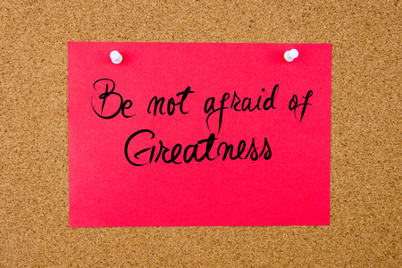 to be or not be: Red paper note with handwritten text Be Not Afraid Of Greatness pinned on cork board with white thumbtacks Stock Photo