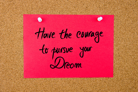 pursue: Red paper note with handwritten text Have The Courage To Pursue Your Dream pinned on cork board with white thumbtacks Stock Photo