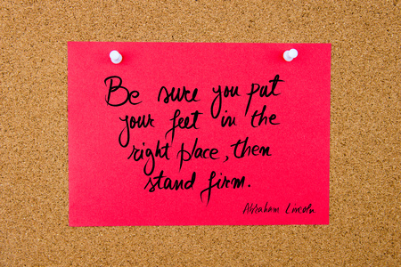 Quote Be Sure You Put Your Feet In The Right Place, Then Stand Firm by Abraham Lincoln, written on red paper note pinned on cork board with white thumbtacks, copy space available