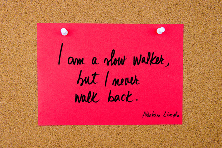 but: Quote I am a slow walker, but I never walk back by Abraham Lincoln, written on red paper note pinned on cork board with white thumbtacks, copy space available
