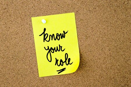 yellow thumbtacks: Know Your Role written on yellow paper note pinned on cork board with white thumbtacks, copy space available Stock Photo