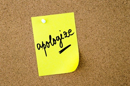 yellow thumbtacks: Apologize written on yellow paper note pinned on cork board with white thumbtacks, copy space available