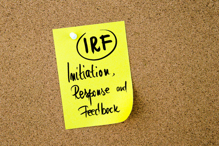 initiation: Business Acronym IRF Initiation, Response and Feedback written on yellow paper note pinned on cork board with white thumbtack, copy space available