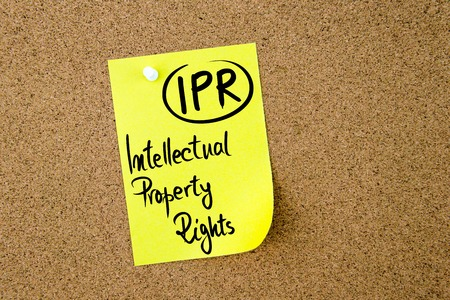 property rights: Business Acronym IPR Intellectual Property Rights written on yellow paper note pinned on cork board with white thumbtack, copy space available