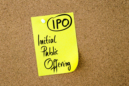 initial public offerings: Business Acronym IPO Initial Public Offering written on yellow paper note pinned on cork board with white thumbtack, copy space available Stock Photo