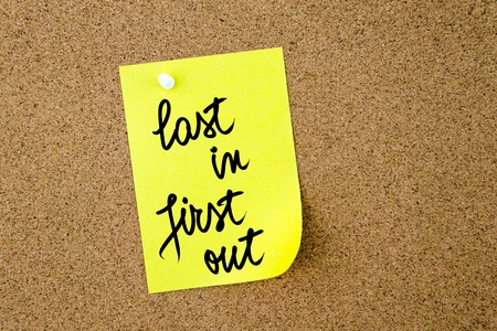 yellow thumbtacks: Last In First Out written on yellow paper note pinned on cork board with white thumbtacks, copy space available Stock Photo