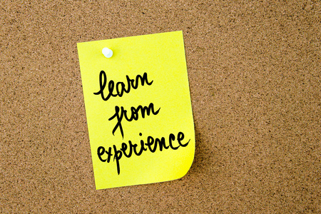 yellow thumbtacks: Learn From Experience written on yellow paper note pinned on cork board with white thumbtacks, copy space available Stock Photo