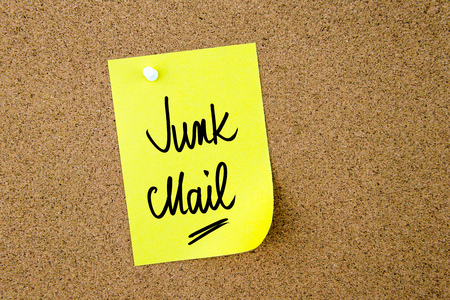 junk mail: Junk Mail written on yellow paper note pinned on cork board with white thumbtacks, copy space available