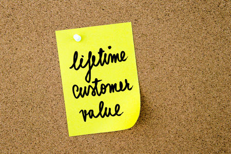 yellow thumbtacks: Lifetime Customer Value written on yellow paper note pinned on cork board with white thumbtacks, copy space available