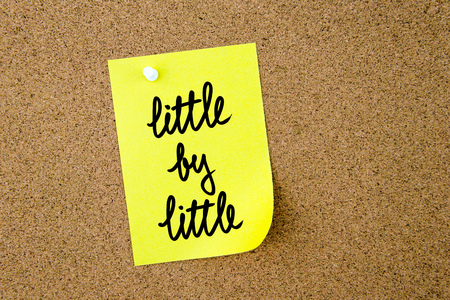 yellow thumbtacks: Little By Little written on yellow paper note pinned on cork board with white thumbtacks, copy space available