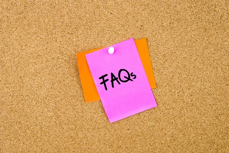 faq's: FAQs  written on paper note pinned on cork board with white thumbtack, copy space available Stock Photo