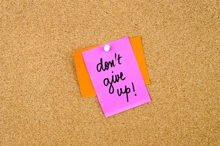 not give: Do Not Give Up written on paper note pinned on cork board with white thumbtack, copy space available