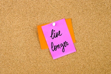 longer: Live Longer written on paper note pinned on cork board with white thumbtack, copy space available Stock Photo