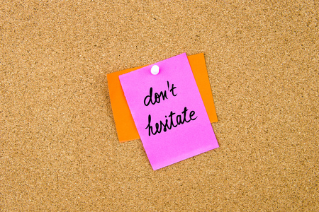 HESITATE: Do Not Hesitate written on paper note pinned on cork board with white thumbtack, copy space available Stock Photo