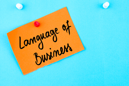 cork sheet: Language Of Business written on orange paper note pinned on cork board with white thumbtack, copy space available