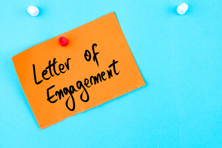 business letters: Letter Of Engagement written on orange paper note pinned on cork board with white thumbtack, copy space available