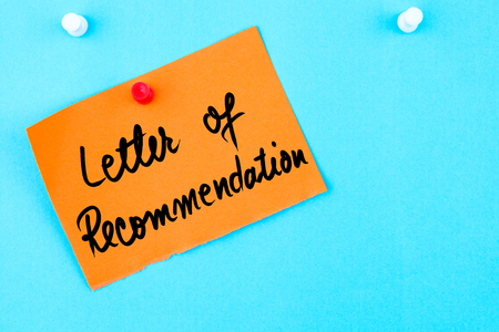 recommendation: Letter Of Recommendation written on orange paper note pinned on cork board with white thumbtack, copy space available