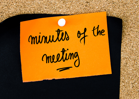 Minutes Of The Meeting written on orange paper note pinned on cork board with white thumbtacks, copy space available Stock Photo