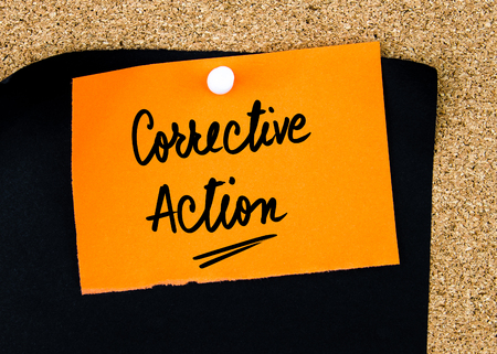 corrective: Corrective Action written on orange paper note pinned on cork board with white thumbtacks, copy space available