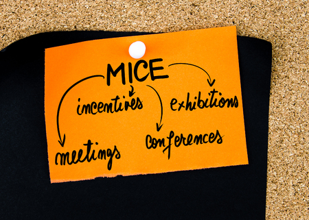 incentives: Business Acronym MICE as Meetings, Incentives, Conferences and Exhibitions written on orange paper note pinned on cork board with white thumbtacks, copy space available
