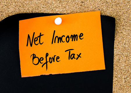 net income: Net Income Before Tax written on orange paper note pinned on cork board with white thumbtacks, copy space available Stock Photo