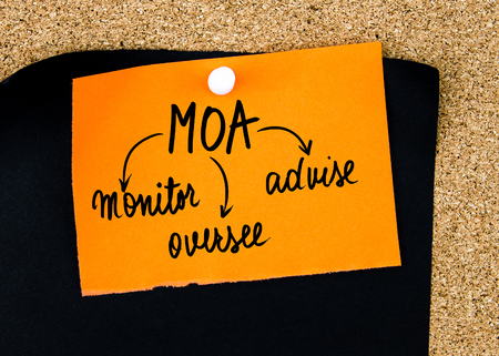oversee: Business Acronym MOA as Monitor, Oversee, Advise written on orange paper note pinned on cork board with white thumbtacks, copy space available Stock Photo