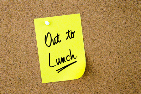 out to lunch: Out To Lunch written on yellow paper note pinned on cork board with white thumbtack, copy space available