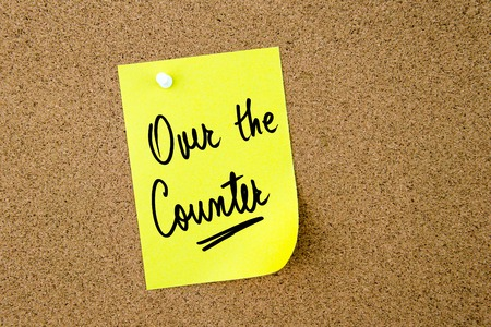 over the counter: Over The Counter written on yellow paper note pinned on cork board with white thumbtack, copy space available Stock Photo