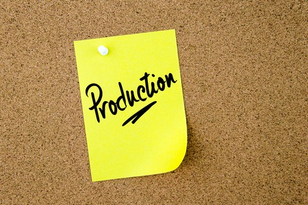 thumbtack: Production written on yellow paper note pinned on cork board with white thumbtack, copy space available