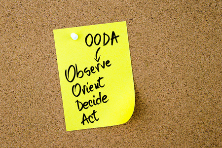 observe: Business Acronym OODA as Observe Orient Decide Act written on yellow paper note pinned on cork board with white thumbtack, copy space available