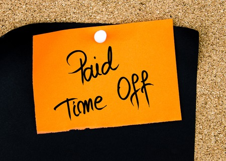 time off: Paid Time Off written on orange paper note pinned on cork board with white thumbtacks, copy space available