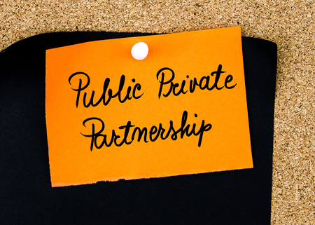 public private: Public Private Partnership written on orange paper note pinned on cork board with white thumbtacks, copy space available
