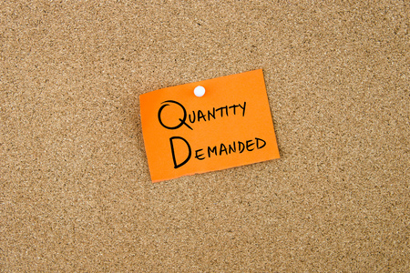 demanded: QUANTITY DEMANDED written on orange paper note pinned on cork board with white thumbtacks, copy space available