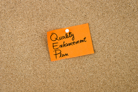 enhancement: Quality Enhancement Plan written on orange paper note pinned on cork board with white thumbtacks, copy space available