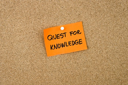 quest: QUEST FOR KNOWLEDGE written on orange paper note pinned on cork board with white thumbtacks, copy space available