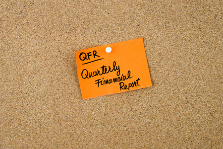 quarterly: QFR as Quarterly Financial Report written on orange paper note pinned on cork board with white thumbtacks, copy space available Stock Photo