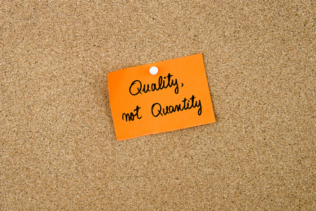 QUALITY, not QUANTITY written on orange paper note pinned on cork board with white thumbtacks, copy space available