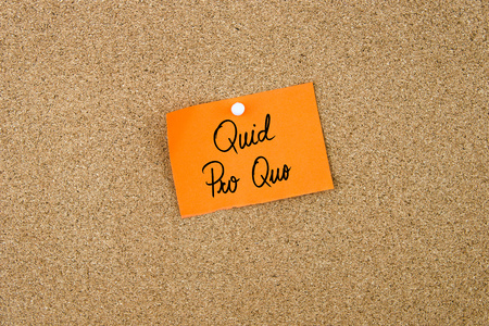 quid: QUID PRO QUO written on orange paper note pinned on cork board with white thumbtacks, copy space available Stock Photo