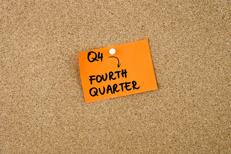 quarter note: Q4 as FOURTH QUARTER written on orange paper note pinned on cork board with white thumbtacks, copy space available