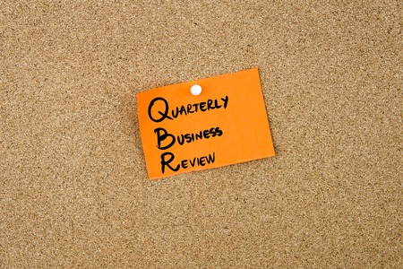 quarterly: QBR as QUARTERLY BUSINESS REVIEW written on orange paper note pinned on cork board with white thumbtacks, copy space available