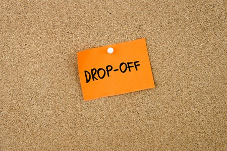 dropoff: DROP-OFF written on orange paper note pinned on cork board with white thumbtacks, copy space available Stock Photo