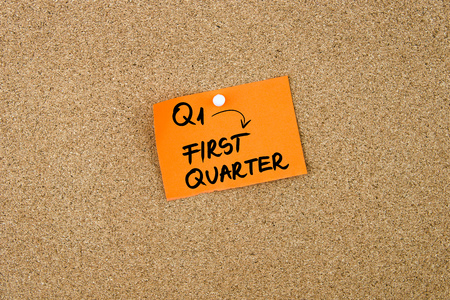 quarter note: Q1 as FIRST QUARTER written on orange paper note pinned on cork board with white thumbtacks, copy space available