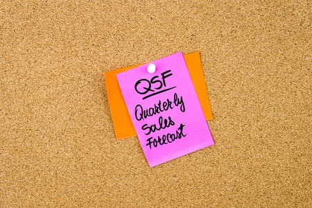 quarterly: Business Acronym QSF Quarterly Sales Forecast written on paper note pinned on cork board with white thumbtack, copy space available