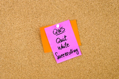 succeeding: Business Acronym QWS Quit While Succeeding  written on paper note pinned on cork board with white thumbtack, copy space available Stock Photo